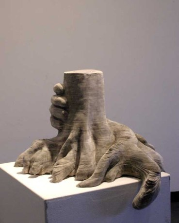 sculpture of a hand grasping a severed tree trunk with tree roots hanging over the plinth